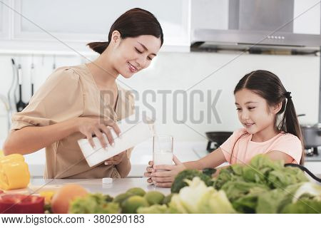 Mother And Child Drinking Milk At The Kitchen