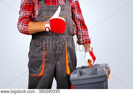 Handyman With Tool Box Thumb Up Against Grey Background.