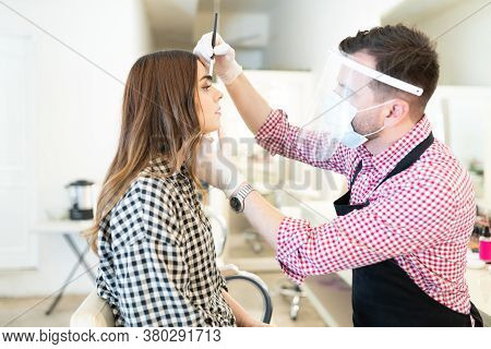 Male Makeup Artist Wearing Face Shield While Applying Eyeshadow On Female Client