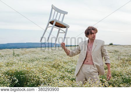 Tall Handsome Man Standing In The Middle Of Camomile Flowers Field And Holding White Chair In Hand