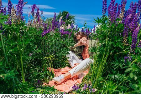 Tall Handsome Man Sitting Among The Lupine Flowers