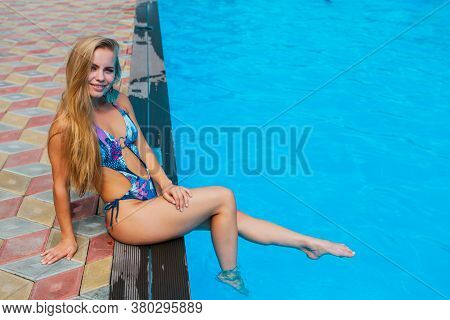 Fashion Portrait Of Beautiful Sexy Young Woman Sitting Near Swimming Pool With Clear Blue Water