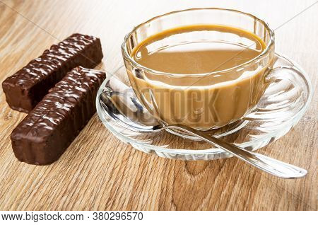 Wafers In Chocolate Glaze, Transparent Cup Of Coffee With Milk, Teaspoon On Saucer On Wooden Table