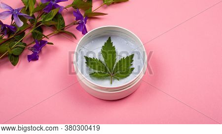 Body Care Cosmetics With Marijuana. White Round Jar With A Body Scrub With A Leaf Of Hemp And Branch