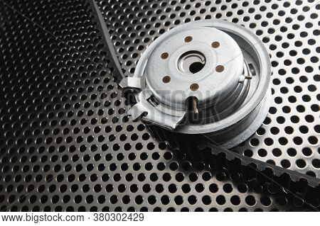 Bearing Tensioner And Timing Belt On A Metal Surface