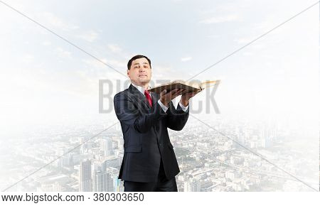 Happy Businessman Holding Open Old Book. Smiling Man In Business Suit Standing On Downtown Backgroun