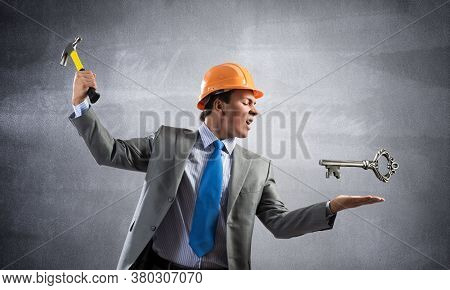 Furious Businessman Going To Crash With Hammer Steel Key. Young Handsome Contractor In Business Suit