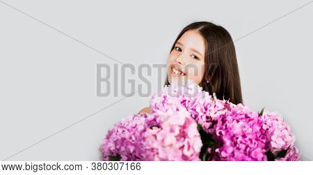 Portrait Of A Smiling Little Girl Holding Flowers. Cute Little Girl On The In Spring Day. Sweet Todd