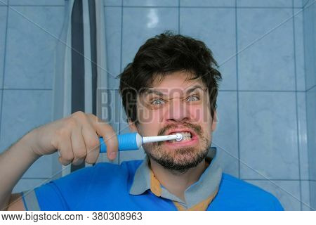 Funny Man Is Brushing Teeth Usin Electric Toothbrush And Making Cheerful Faces. Dental Oral Hygiene