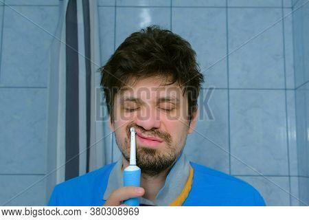 Sleepy Shaggy Drunken Man With Hangover Trying To Brush Teeth Using Electric Brush In Bathroom.