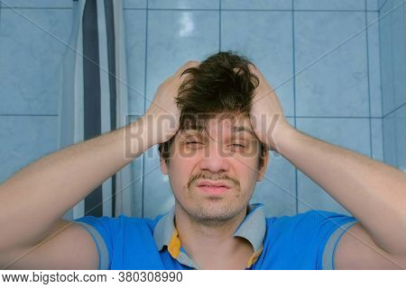 Depressed Shaggy Young Man With Headache And Hangover In Bathroom In Morning Rubs His Face. Portrait