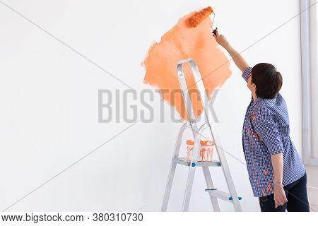Happy Middle-aged Woman Painting Interior Wall With Paint Roller In New House. A Woman With Roller A