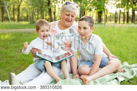 Children And Grandma Having Fun Outdoors. Senior Woman Showing The Family Album. Loving Grandmother