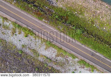 Aerial View Top Down Photo From Flying Drone Of Asphalt Road Around The Dam And People Running Exerc