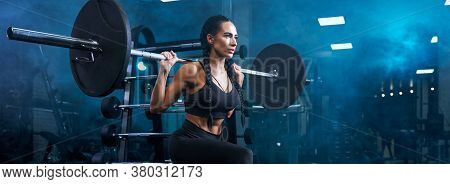 Stunning Brunette Female With Long Braids Doing Squats Using Barbell, Panoramic. Side View Of Concen