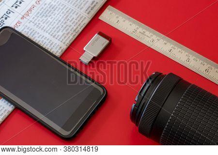 Bankura, West Bengal, India - March 9, 2019: Bengali News Paper Pen Drive Mobile Nikon Lens And Rule