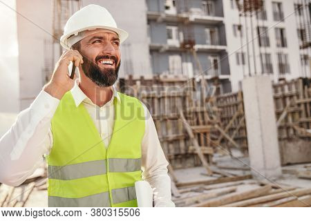 Happy Confident Bearded Male Inspector In Hardhat Standing On Construction Site Of Contemporary Resi