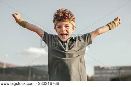 Low Angle Of Excited Little Boy With Arms Raised Jumping And Smiling Happily While Celebrating Succe