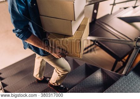 Partial View Of Businessman Holding Carton Boxes And Walking On Stairs In Office