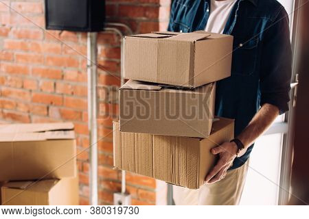 Partial View Of Businessman Holding Carton Boxes While Walking In New Office