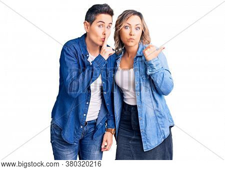 Couple of women wearing casual clothes asking to be quiet with finger on lips pointing with hand to the side. silence and secret concept.