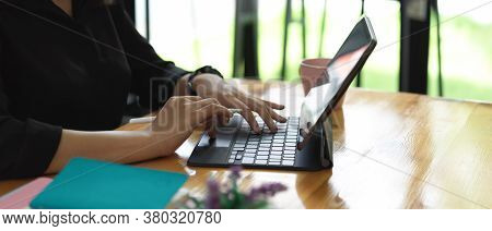 Side View Of Female Hands Typing On Tablet Keyboard On Worktable In Glass Wall Office Room