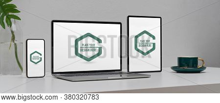 Mock Up Digital Devices On Worktable With Smartphone, Laptop And Digital Tablet