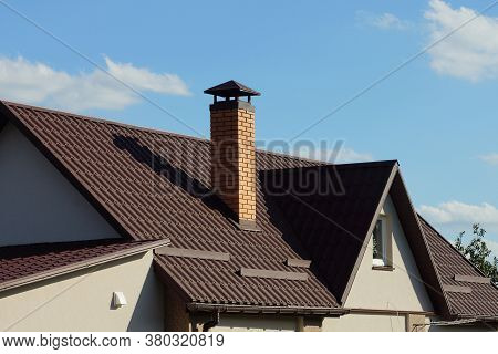 Brown Tiled Roof Of A Gray Private House With A Window And One Brick Chimney Against A Blue Sky