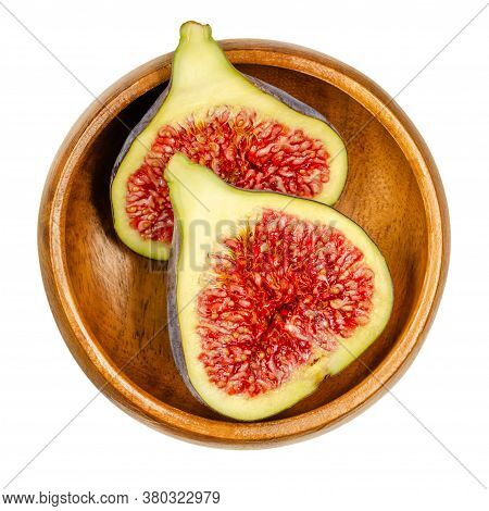 Fresh Fig Cut In Two Halves, In A Wooden Bowl. Fruit With Purple Skin And Red Flesh. Common Figs Can