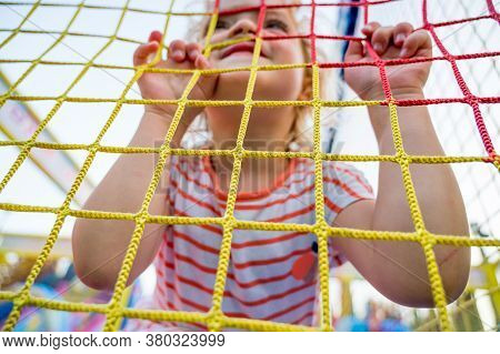 Cute Blonde Girl Leaning On Safety Fence In Outdoor Playground.