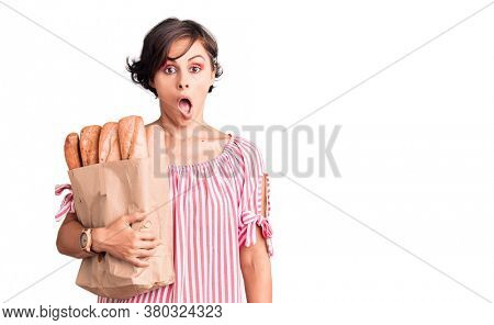 Beautiful young woman with short hair holding paper bag with bread scared and amazed with open mouth for surprise, disbelief face
