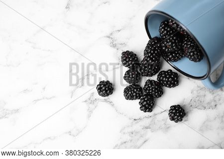 Overturned Mug With Blackberries On White Marble Table, Flat Lay. Space For Text