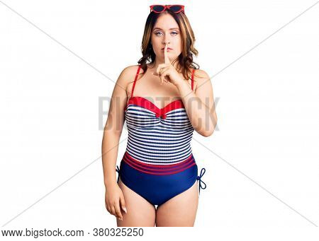 Young beautiful caucasian woman wearing swimwear asking to be quiet with finger on lips. silence and secret concept.