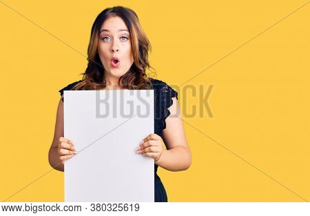 Young beautiful caucasian woman holding cardboard banner with blank space scared and amazed with open mouth for surprise, disbelief face