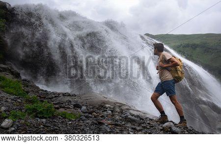 Waterfall Landscape And Male Traveler Enjoying Waterfall View.