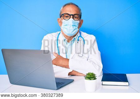 Senior handsome man with gray hair wearing doctor uniform and medical mask skeptic and nervous, disapproving expression on face with crossed arms. negative person.