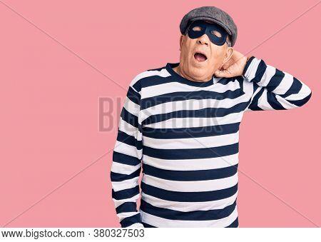 Senior handsome man wearing burglar mask and t-shirt suffering of neck ache injury, touching neck with hand, muscular pain