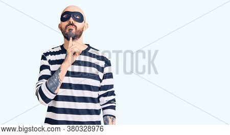 Young handsome man wearing burglar mask thinking concentrated about doubt with finger on chin and looking up wondering