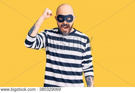 Young handsome man wearing burglar mask angry and mad raising fist frustrated and furious while shouting with anger. rage and aggressive concept.