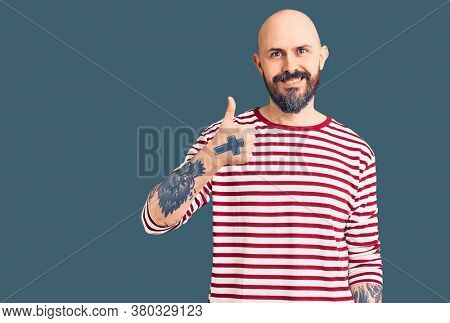 Young handsome man wearing casual clothes doing happy thumbs up gesture with hand. approving expression looking at the camera showing success.