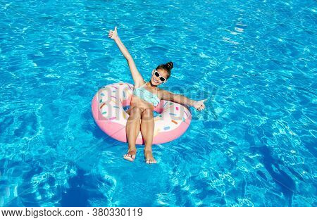 Cute Smiling Little Girl In Swimming Pool With Rubber Ring. Child Having Fun On Vacation In Summerti