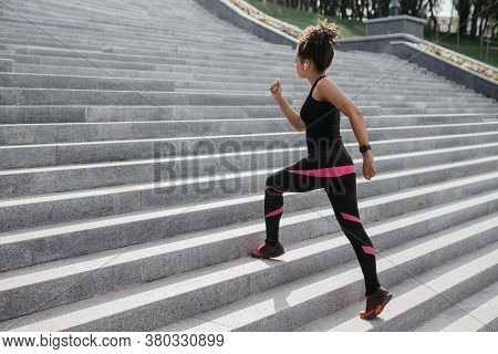 Muscle Training. Fashion African American Girl In Sportswear With Headphones And Fitness Tracker Run