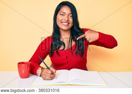 Beautiful latin young woman with long hair writing a book sitting on the table pointing finger to one self smiling happy and proud