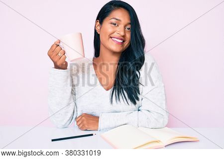 Beautiful latin young woman with long hair reading a book and drinking a coffee looking positive and happy standing and smiling with a confident smile showing teeth