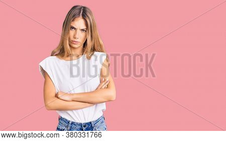 Beautiful caucasian woman with blonde hair wearing casual white tshirt skeptic and nervous, disapproving expression on face with crossed arms. negative person.