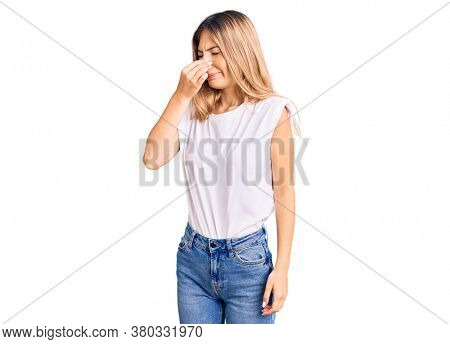 Beautiful caucasian woman with blonde hair wearing casual white tshirt smelling something stinky and disgusting, intolerable smell, holding breath with fingers on nose. bad smell