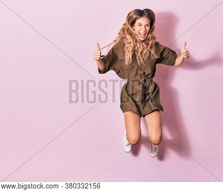 Young beautiful woman wearing casual clothes smiling happy. Jumping with smile on face doing ok sig with thumbs up over isolated pink background