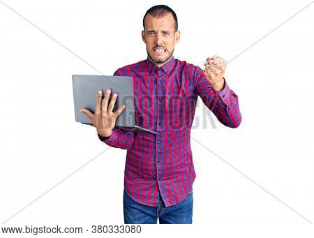 Young handsome man working using computer laptop annoyed and frustrated shouting with anger, yelling crazy with anger and hand raised