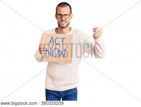 Young handsome man holding act now banner annoyed and frustrated shouting with anger, yelling crazy with anger and hand raised