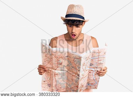 Young hispanic man wearing summer hat holding map scared and amazed with open mouth for surprise, disbelief face